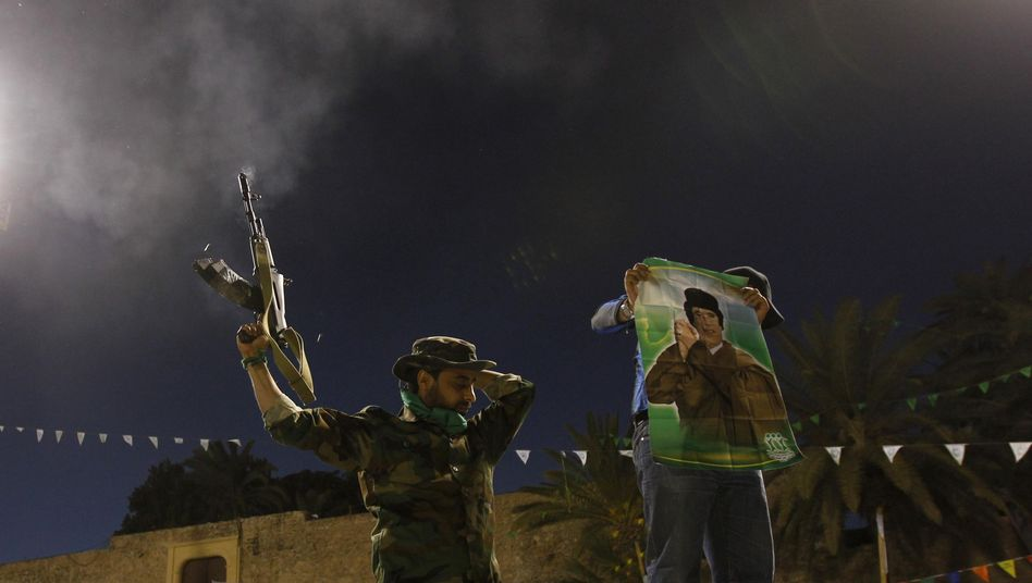 A Libyan army soldier loyal to Muommar Gadhafi fires shots in the air on Sunday as Western forces pound the country's air defenses and patrol its skies.