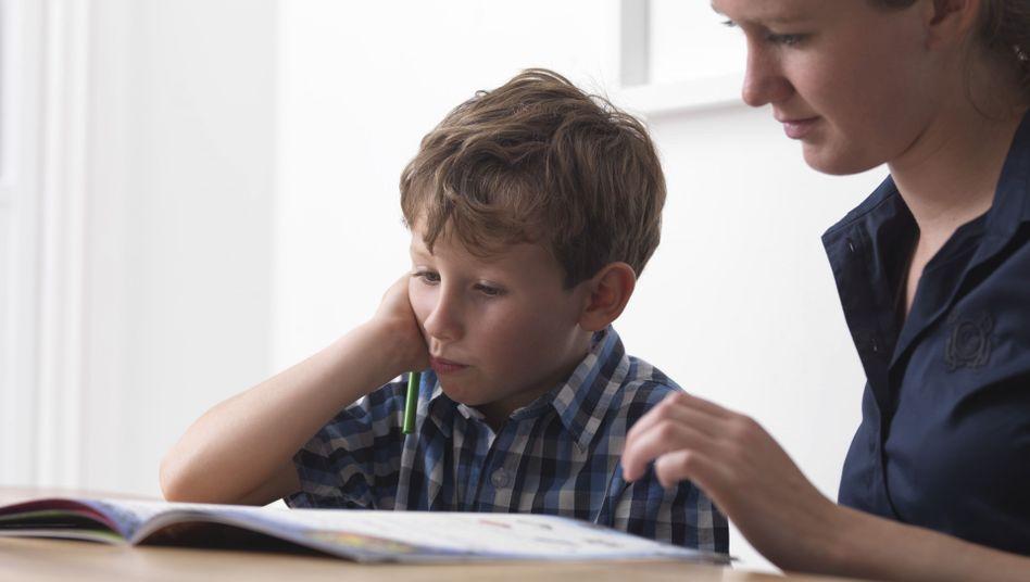Junge brütet über Hausaufgaben - mithilfe einer Erwachsenen