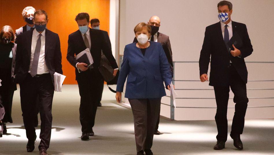 Kanzlerin Merkel nach der letzten Ministerpräsidentenkonferenz mit dem aktuellen MPK-Chef Michael Müller (l.) und seinem Stellvertreter Markus Söder