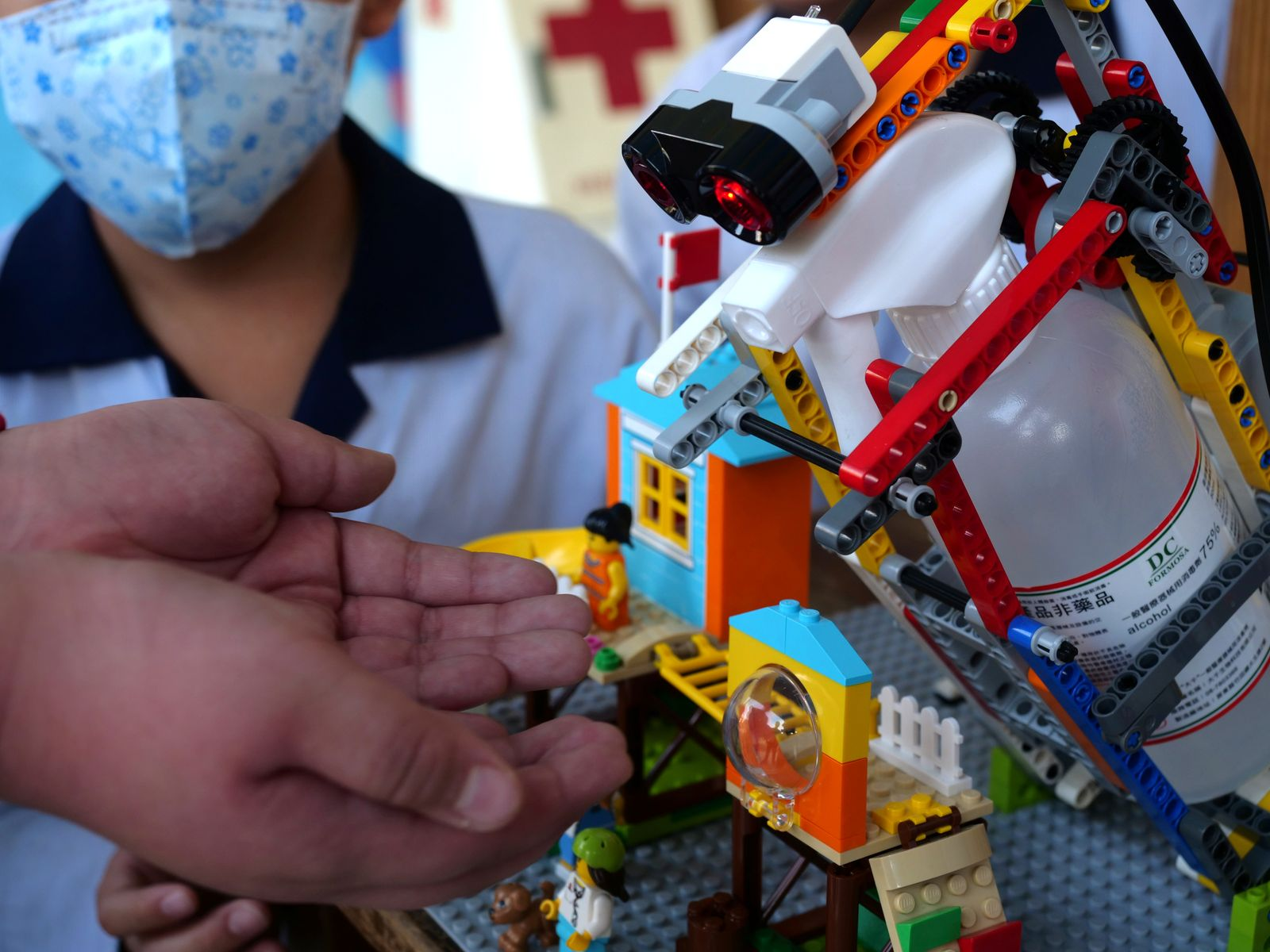 Elementary school student uses a self-built motion sensor controlled disinfectant dispenser assembled with Lego parts, following a novel coronavirus outbreak, in the southern Taiwanese city of Kaohsiung, Taiwan