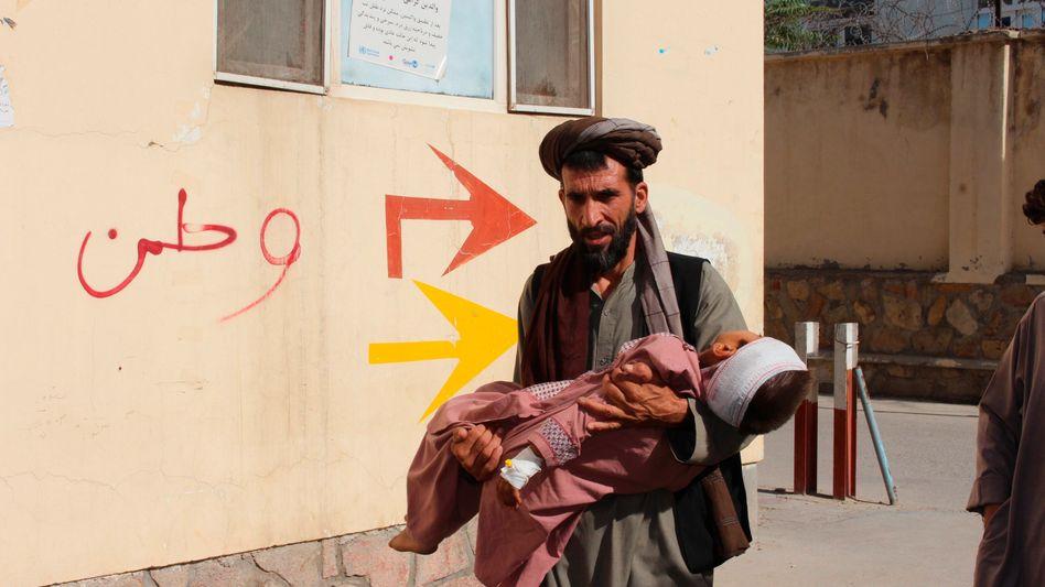 Ein afghanischer Mann bringt ein Kind zu einem Krankenhaus. Das Kind wurde bei Kämpfen in der Provinz Badghis verwundet