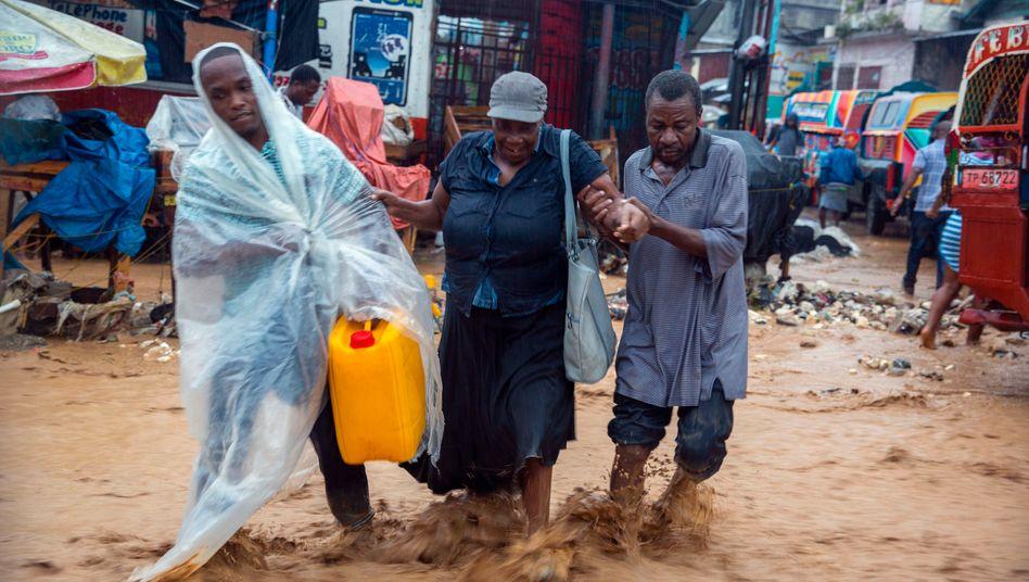 """Gefahr durch Tropensturm """"Laura"""": Straßenverkäufer in einer überschwemmten Straße in Haiti"""