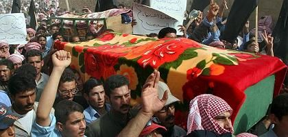 Syrians carry the coffin of one of the victims of Sunday's US raid inside Syrian territory.