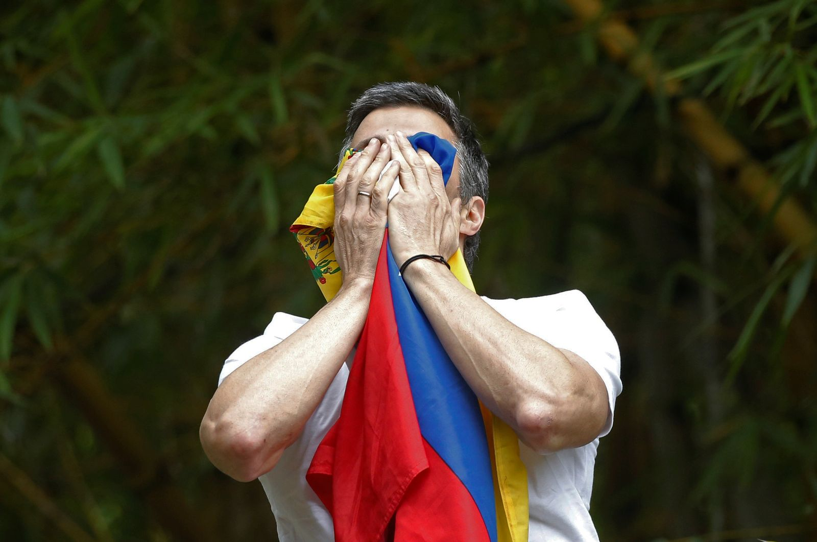 Venezuela's opposition leader Leopoldo Lopez, who has been granted house arrest after more than three years in jail, salutes supporters, in Caracas