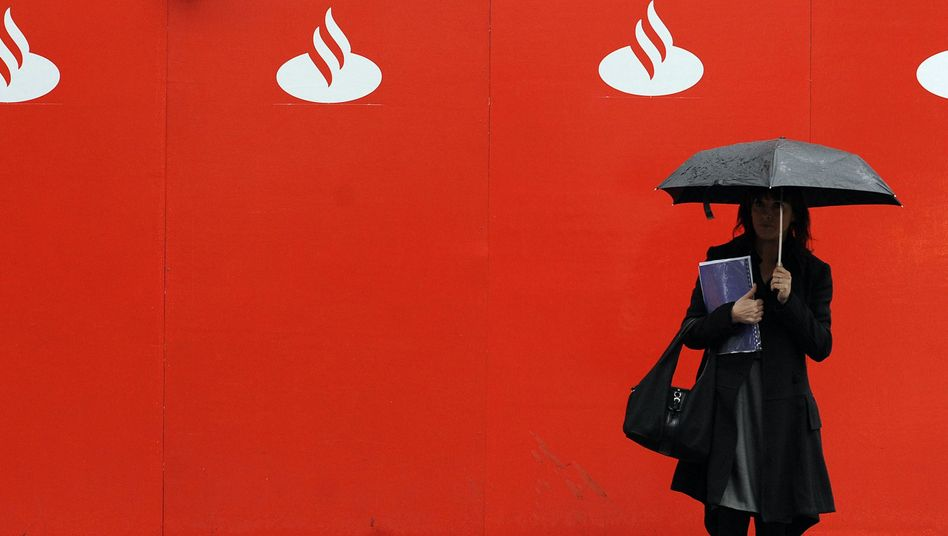 A woman standing under a logo of the Spanish bank Santander. Madrid wants to reveal the results of stress tests performed on large European banks.