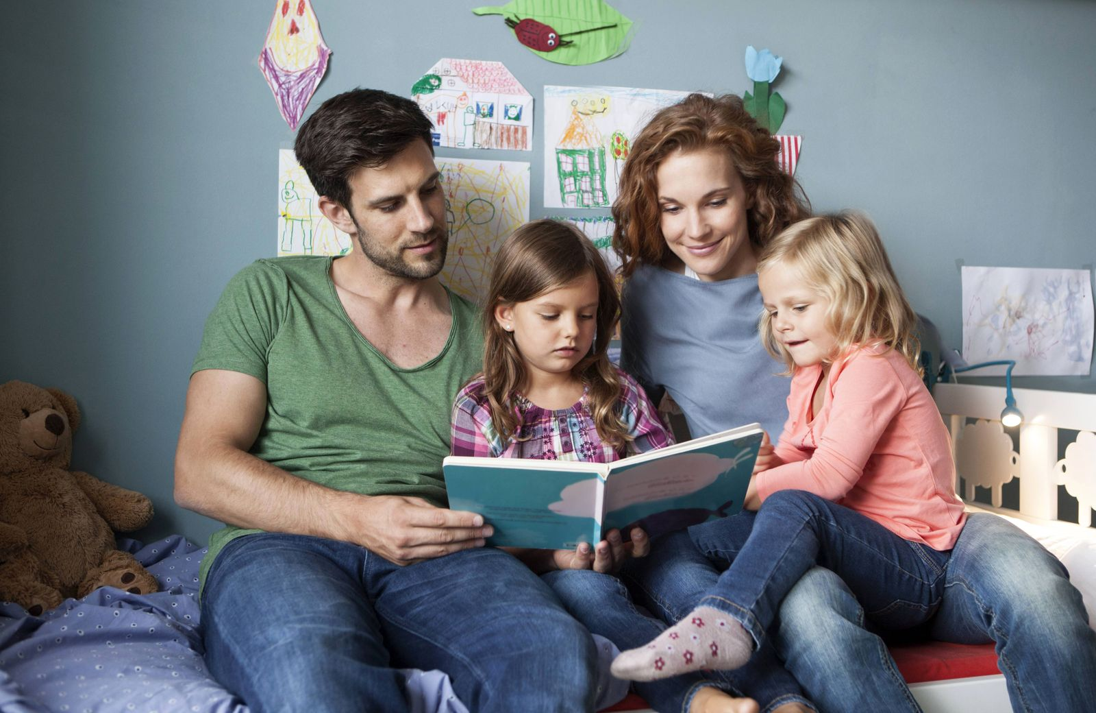 Couple and little daughters sitting together on bed in children s room reading a book model released Symbolfoto propert
