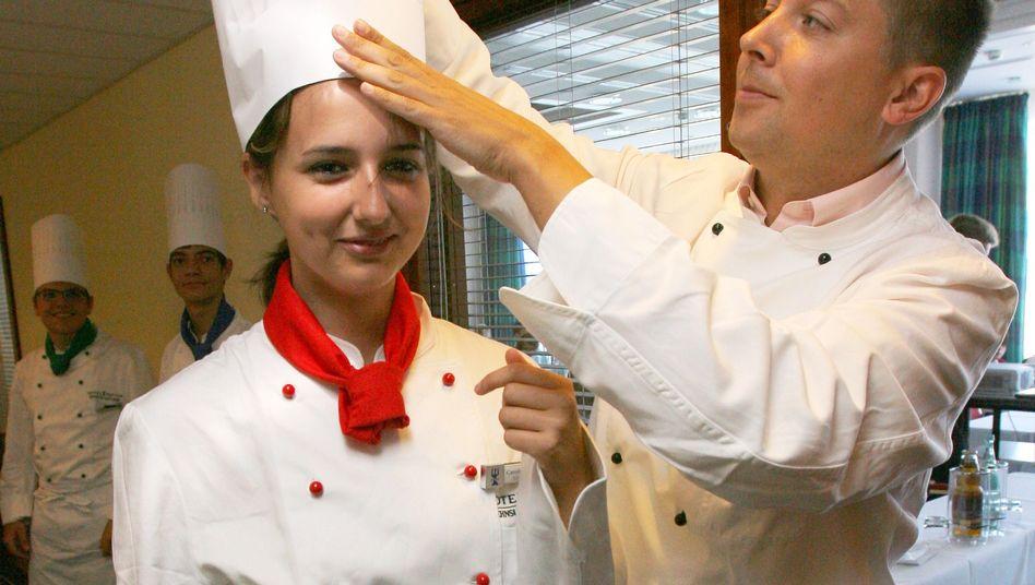 Ausbildung mit großem Hut: Eine junge Frau beginnt ihre Lehre im Hotelrestaurant