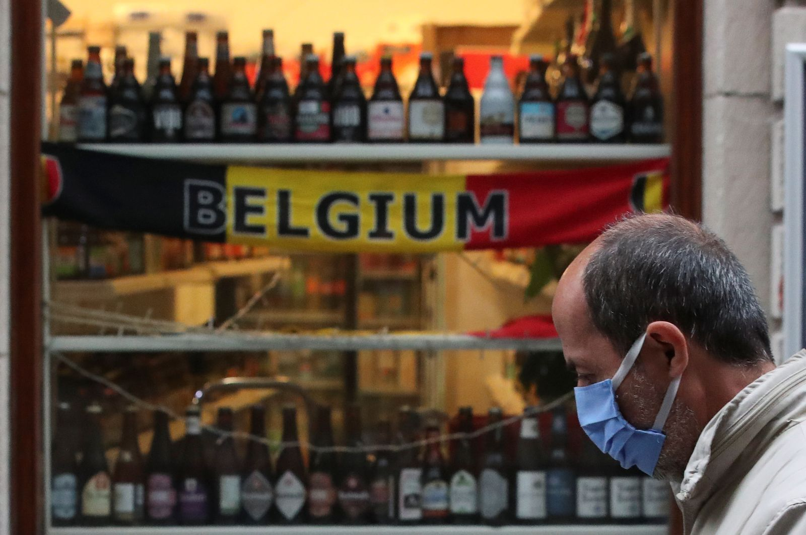A man wearing a face mask walks past a shop selling beers, as the spread of the coronavirus disease (COVID-19) continues, in central Brussels