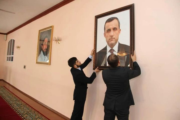 """Afghan embassy staff hanging a portrait of Afghan First Vice President Amrullah Saleh, who declared himself the """"legitimate caretaker president,"""" on the wall at the embassy in Dushanbe, Tajikistan."""