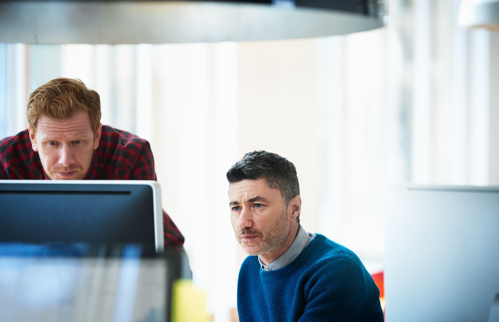 Two colleagues contemplating a project on computer