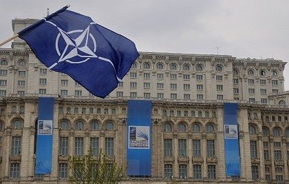 A NATO flag billows in front of the parliamentary building in Bucharest, where the 26 NATO leaders are due to meet for their three day summit.