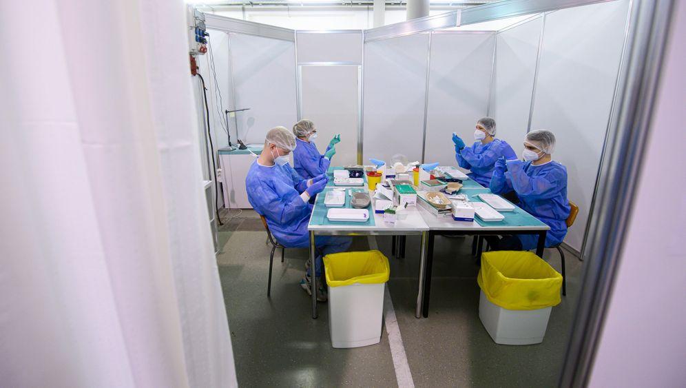 Mitarbeitende eines Impfzentrums beim Aufziehen der Impfspritzen (20. März 2020)