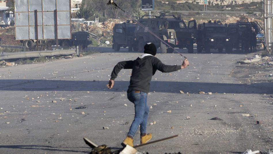 Ein Palästinenser wirft Steine auf israelische Sicherheitskräfte.