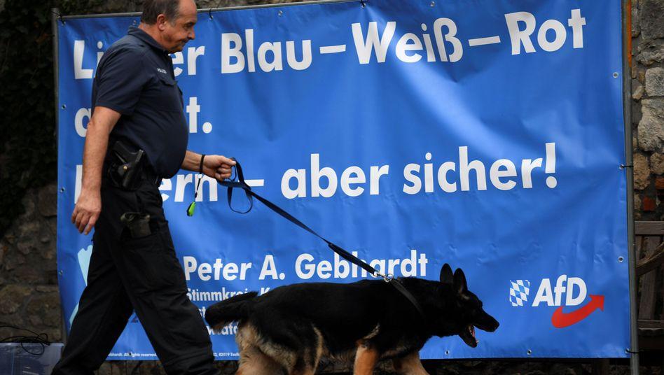 Polizist vor AfD-Plakat