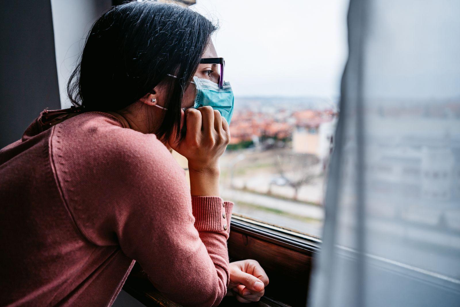 Woman in quarantine looking through the window