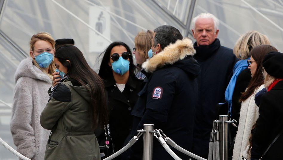 Touristin vor dem Pariser Louvre am Freitag: Das Museumspersonal streikt aus Angst vor dem Virus