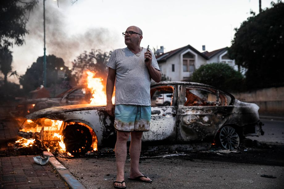 A Lod resident in front of his burning car.