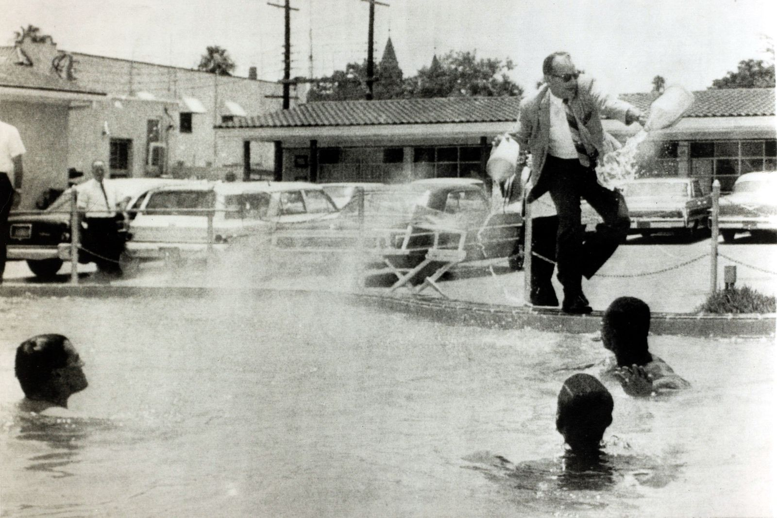 """Racial Discrimination Segregation, USA. pic: 18th June 1964. St.Augustine, Florida. Demonstrators black and white stage a """"jump-in"""" at a motel pool, open only whites, as the angry motel manager dumps the contents of two containers marked """"muriatic acid"""""""