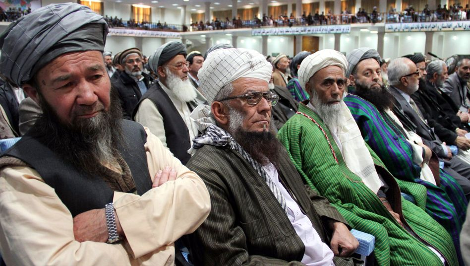 Afghan delegates listen to a speech by President Hamid Karzai in Afghanistan in November.