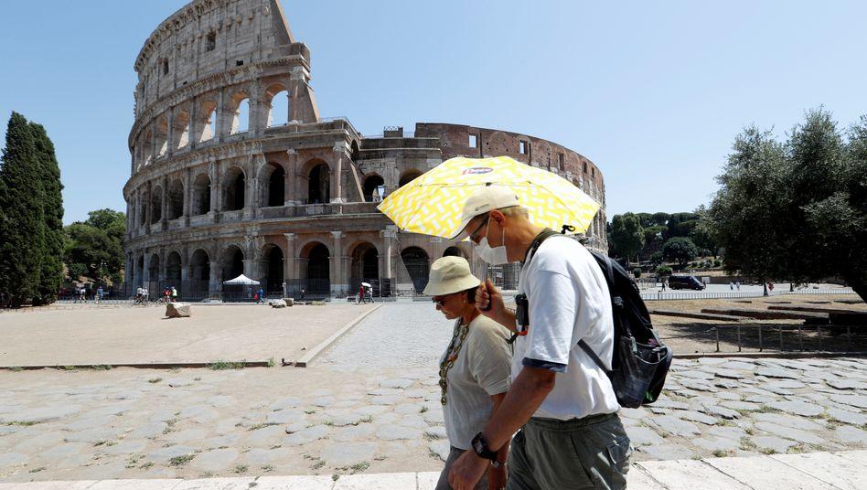 Passanten laufen mit Mundschutz vor dem Kolosseum in Rom vorbei
