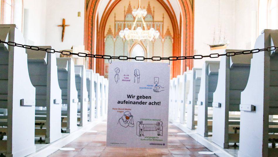 """Plakat mit Corona-Regeln in der Inselkirche Langeoog: """"Wir geben aufeinander acht"""""""