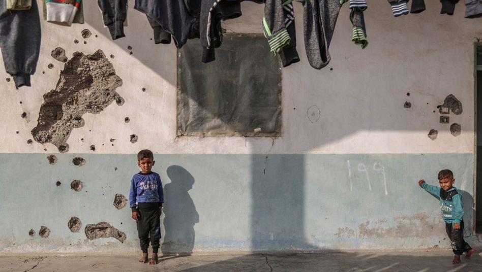 Syrische Kinder spielen vor einem Haus in Tall Abjad, dessen Wand durch Einschusslöcher beschädigt ist