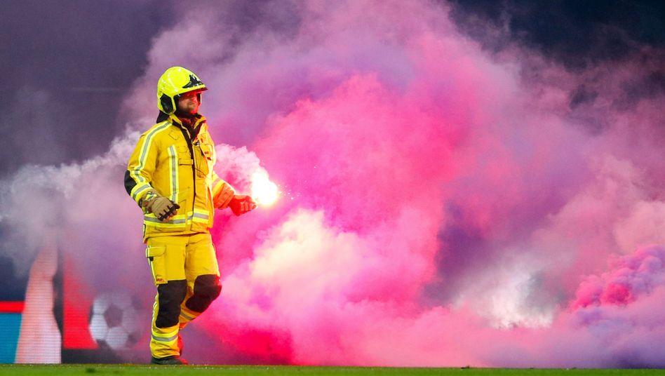Ein Feuerwehrmann entfernt die Pyrotechnik vom Spielfeld in Lüttich