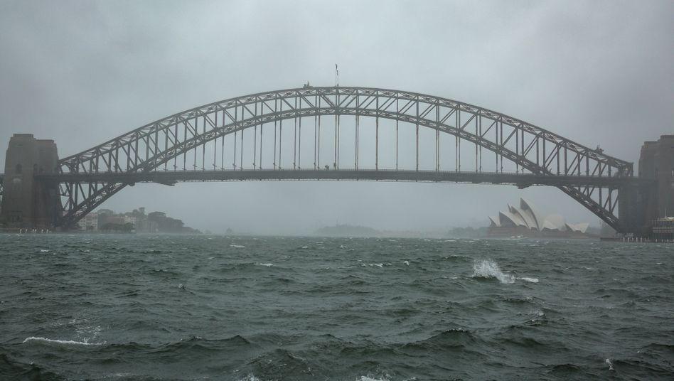 Sydneys Harbour Bridge und die Oper im Regen, der Wind hat das Wasser im Hafen aufgepeitscht
