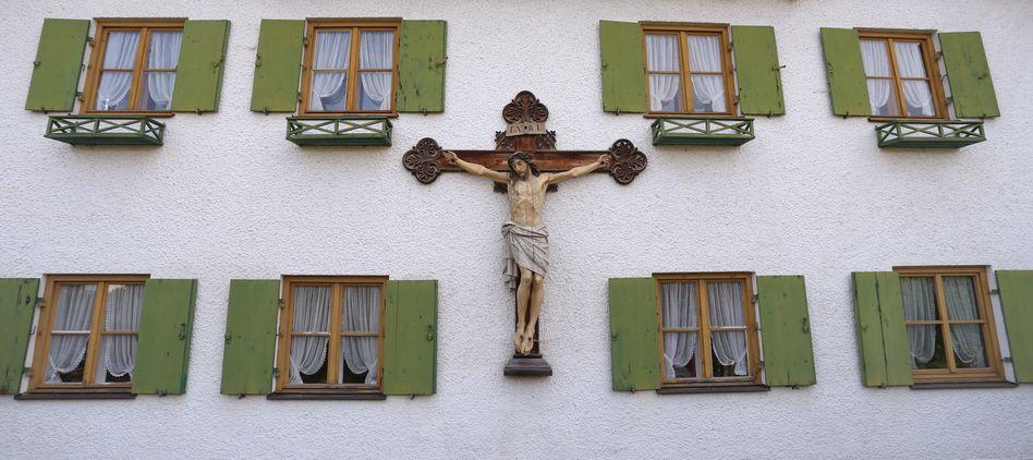 Ein Kruzifix an der Außenwand eines Bauernhauses