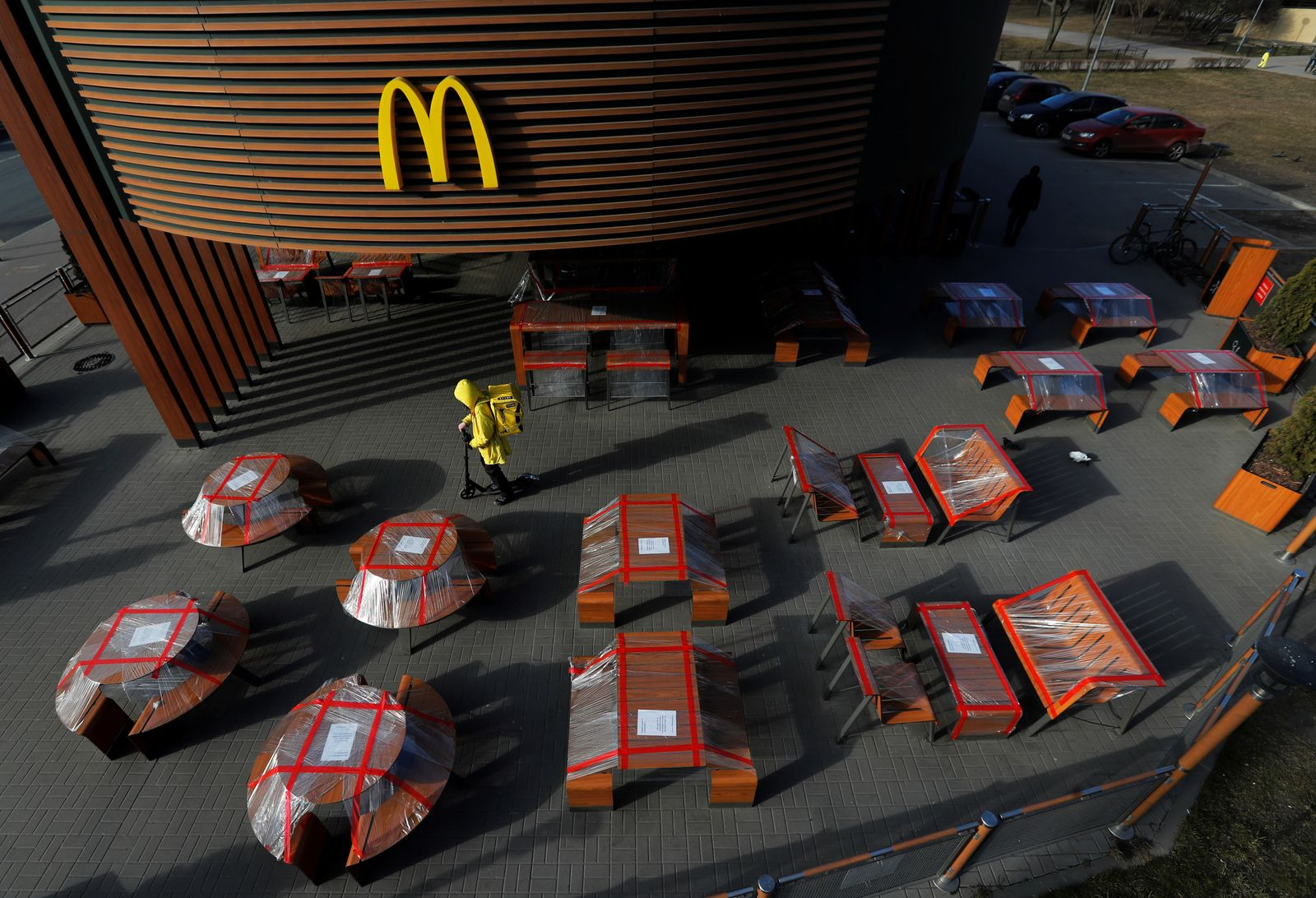 Food delivery courier rides a scooter among plastic-wrapped tables of McDonald's restaurant in Saint Petersburg