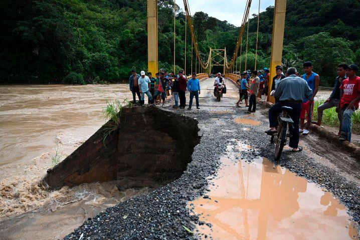 Menschen stehen in Guatemala an einer beschädigten Straße, die zu einer Brücke führt