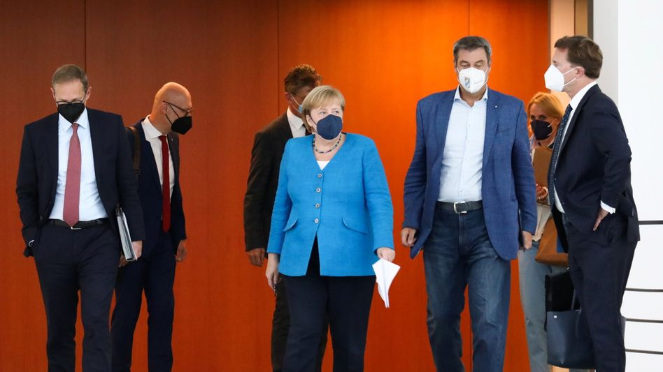 MPK-Chef Müller (l.) und sein Vize Söder (r.), dazwischen Kanzlerin Merkel