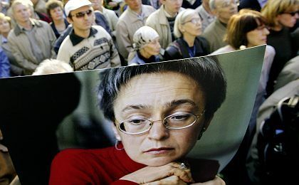 People hold up a portrait of murdered journalist Anna Politkovskaya during a rally marking what would have been her 49th birthday.