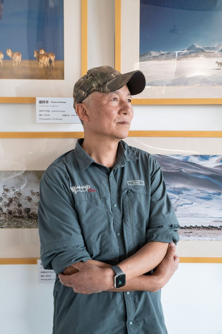 Wildlife filmmaker Xi Zhinong in his studio in Dali, with some of his photos on the wall behind him.