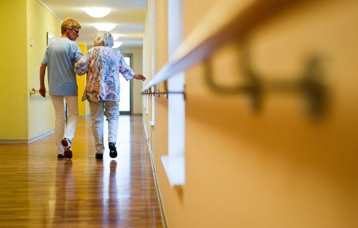 Eine Pflegerin begleitet eine ältere Dame durch den Korridor eines Pflegeheims in Stuttgart