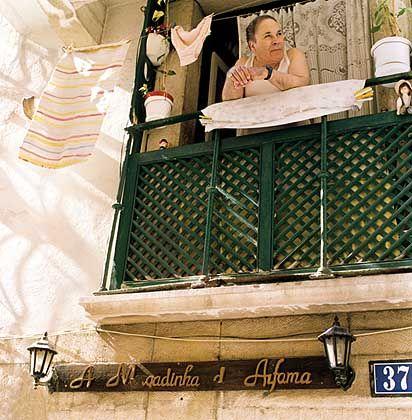 Alfama: Von seinem Logenplatz auf dem Balkon, zwischen Topfpflanzen, Kochwäsche und Nippesfiguren, genießt dieser Mann die Mittagsruhe in der Rua de Reguira
