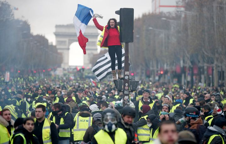 A protester wearing yellow vest, a symbol of a French drivers' protest against higher fuel prices, stands on the red light on the Champs-Elysee in Paris, France, November 24, 2018. REUTERS/Benoit Tessier - RC17FB1DAB40