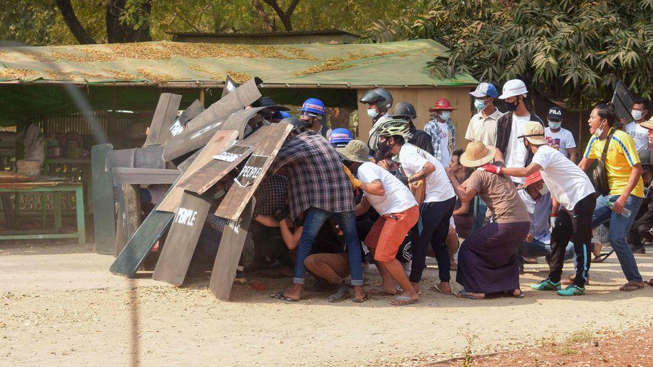 Demonstrierende schützen sich vor Sicherheitskräften: Eskalation in Myanmar
