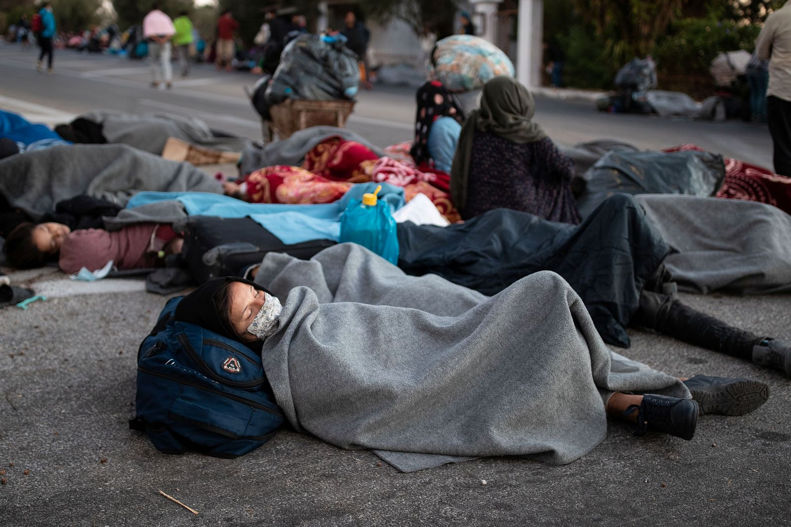 Refugees and migrants sleep on a road following a fire at the Moria camp on the island of Lesbos