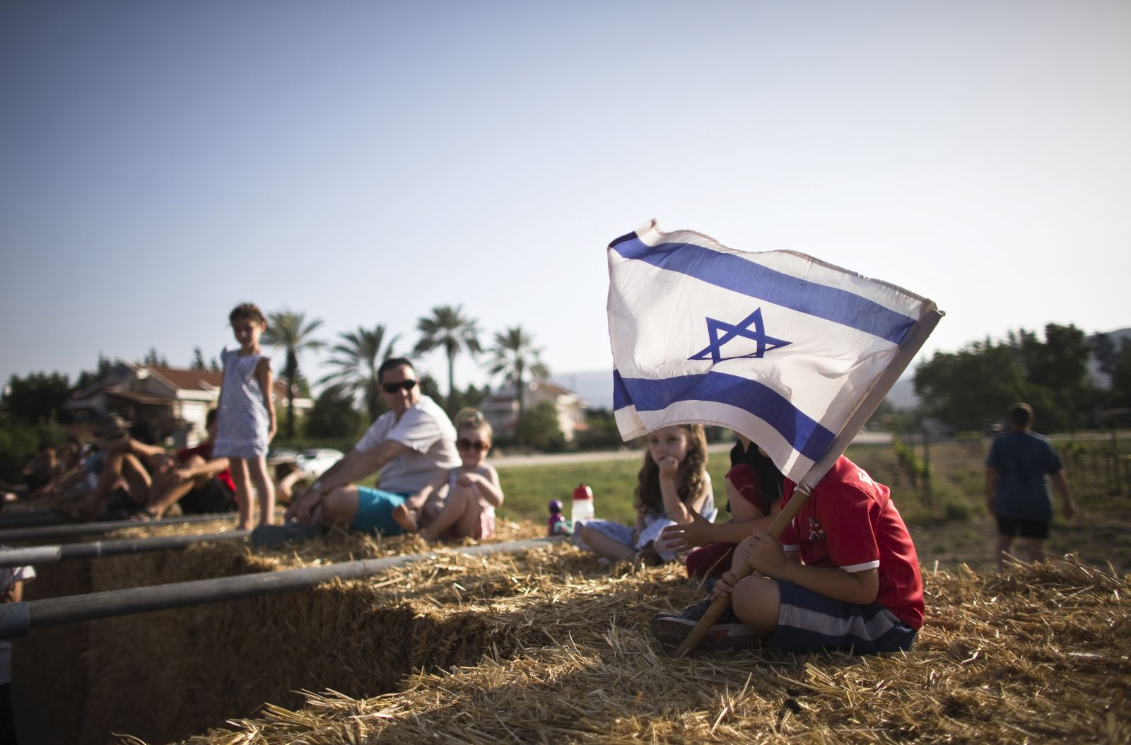 Children sit on bales of hay at the annual harvest festival in Kibbutz Degania Alef, northern Israel