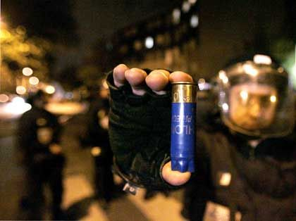 A French policeman holds a shotgun shell recovered on Sunday night after officers were fired on by rioters.