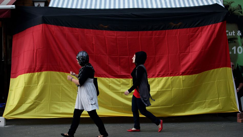 Two young Muslim women walk by a pub in the Berlin neighborhood of Neukoelln draped in a German flag during the 2010 soccer World Cup: A lack of a proper immigration policy in Germany in the past led to today's problems with integration.