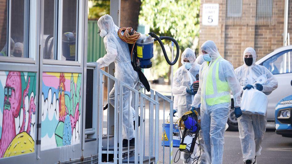 Reinigungskräfte gehen in Schutzkleidung in eine Schule in Sydney