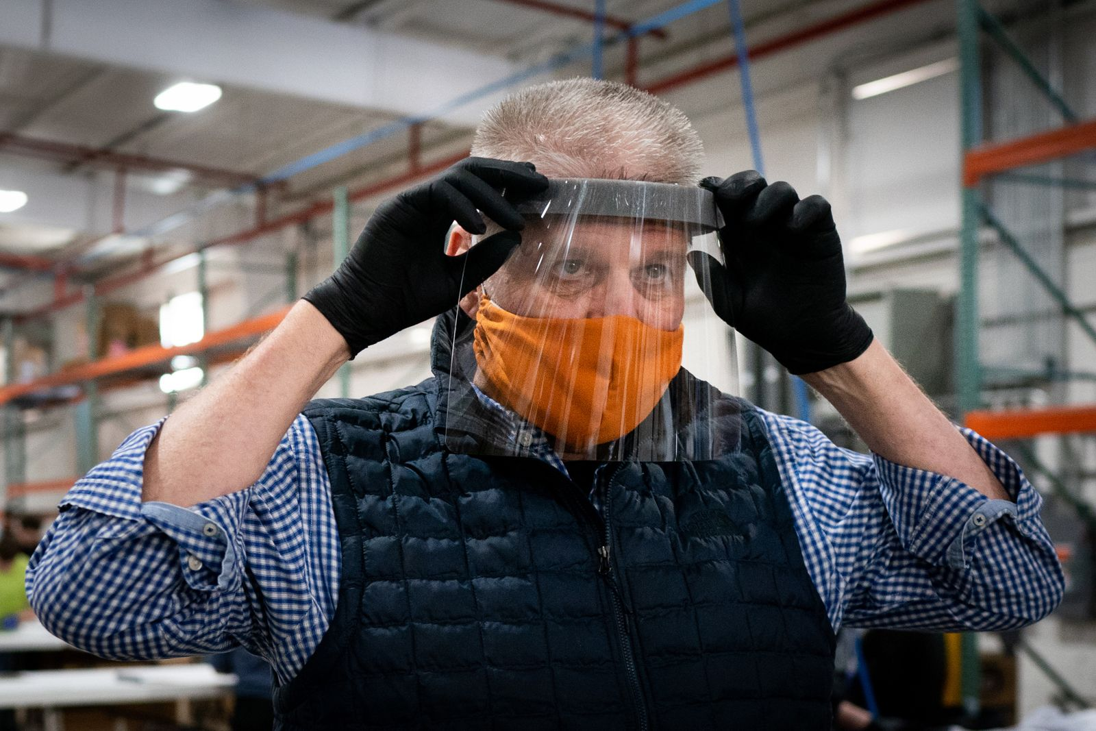 Sam Yoder, the owner of Berlin Gardens in Millersburg, Ohio, demonstrates a face shield, April 3, 2020, that the company is manufacturing. (Erin Schaff/The New York Times)