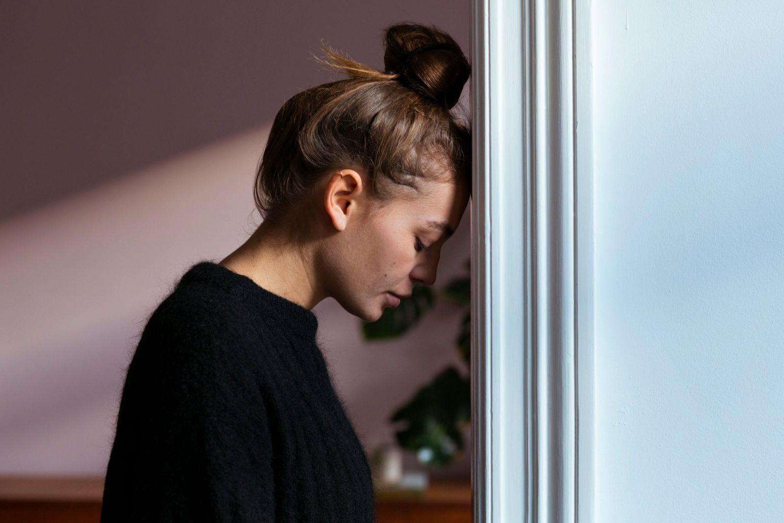 Junge Frau lehnt erschöpft am Türrahmen