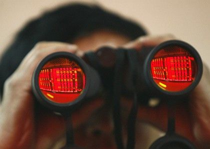A man uses binoculars to monitor stock movements at a stock exchange in Shenyang.