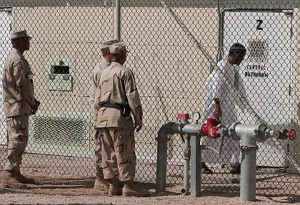 A group of US soldiers observe a detainee at the facility at Guantanamo Bay on Cuba.