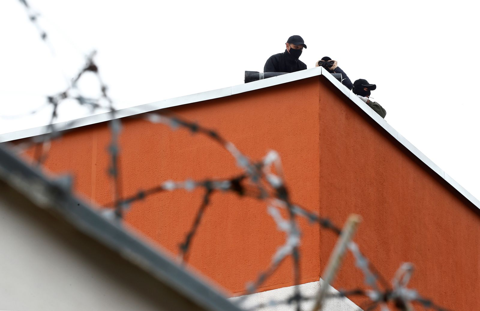 Servicemen of the Belarusian Interior Ministry watch from the roof of a detention centre in Minsk