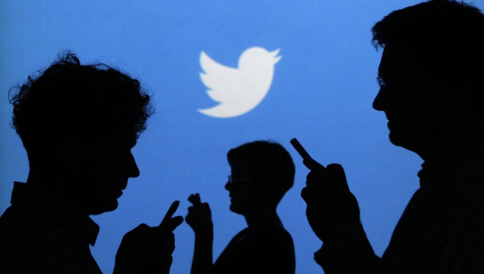 Smartphone-Nutzer vor Twitter-Symbol: 255 Millionen Nutzer im Monat