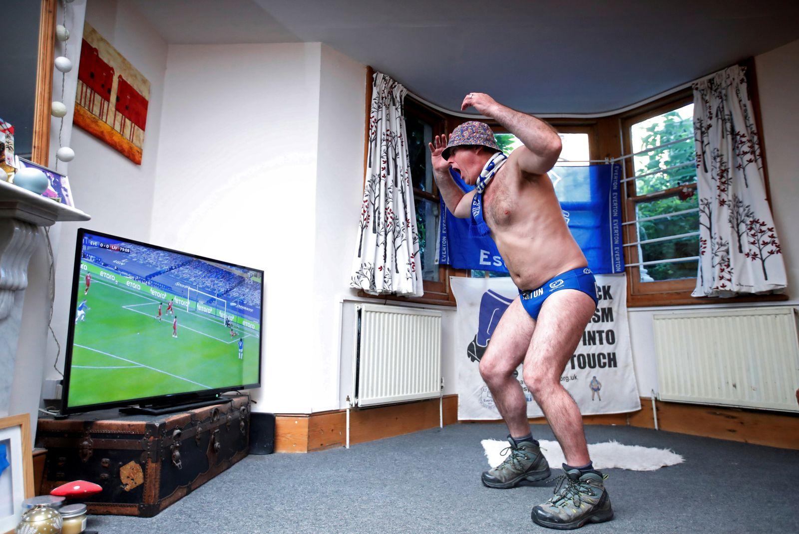 Fans watch the return of the Premier League - Everton v Liverpool